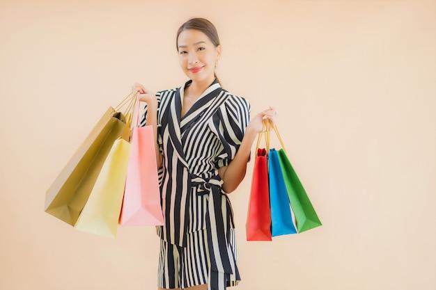 Женщина портрета красивая молодая азиатская с много хозяйственной сумкой