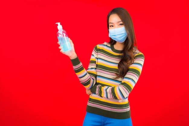 Bella giovane donna asiatica del ritratto con il gel dell'alcool sulla parete isolata rossa