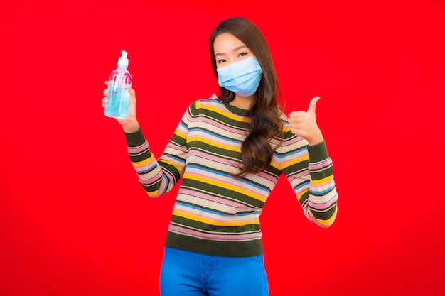 Portrait beautiful young asian woman with alcohol gel on red isolated wall