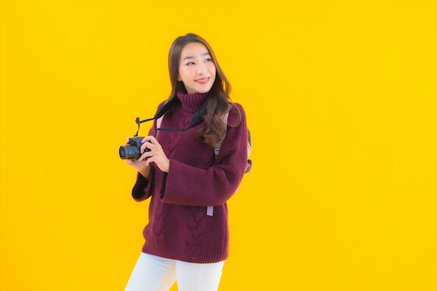 休暇旅行のためのバックパックとカメラと肖像画の美しい若いアジアの女性