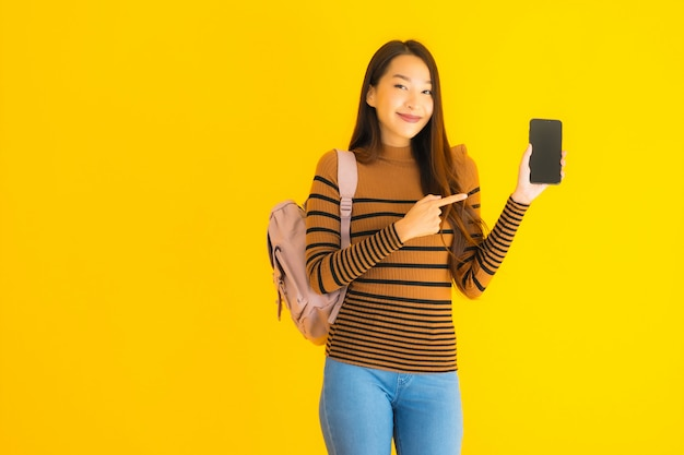 Portrait beautiful young asian woman with bagpack uses smartphone