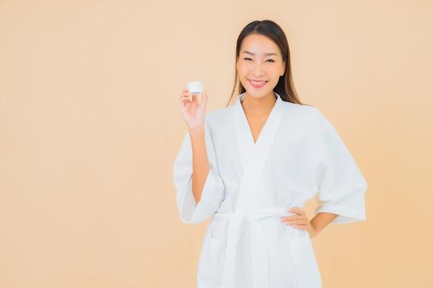 ベージュのボトルローションとフェイスクリームと肖像画の美しい若いアジアの女性