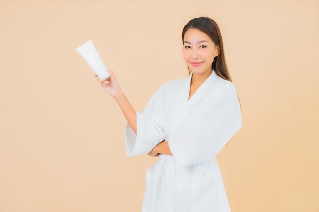 Bella giovane donna asiatica del ritratto con lozione della bottiglia e crema per il viso sul beige