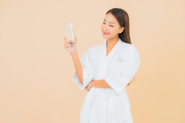 Bella giovane donna asiatica del ritratto con acqua in bottiglia per bere sul beige