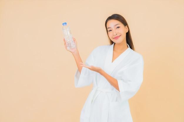 ベージュの飲み物のボトルウォーターと肖像画美しい若いアジアの女性