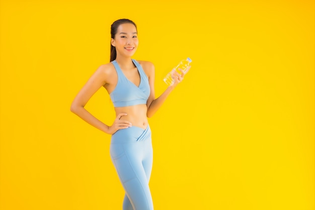 Portrait beautiful young asian woman with bottle water on yellow