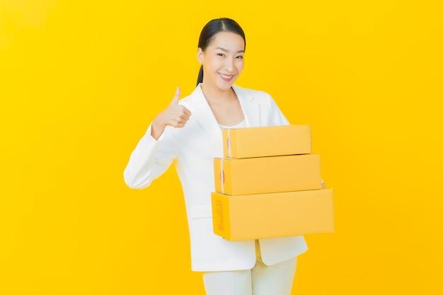 Женщина портрета красивая молодая азиатская с коробкой, готовой для доставки на стене цвета