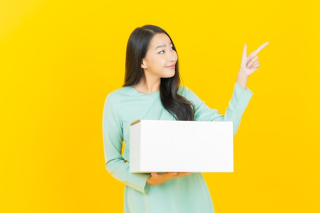 黄色で出荷する準備ができて箱を持つ肖像画の美しい若いアジアの女性