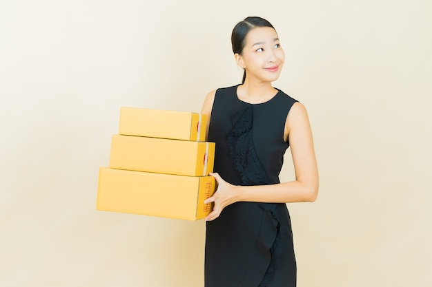 Portrait beautiful young asian woman with box ready for shipping on color wall