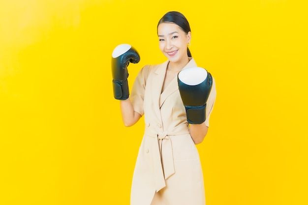 Portrait beautiful young asian woman with boxing glove on color wall