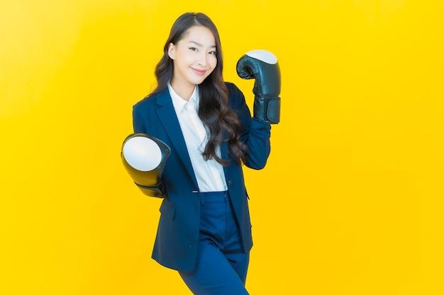 Ritratto bella giovane donna asiatica con guantoni da boxe su giallo
