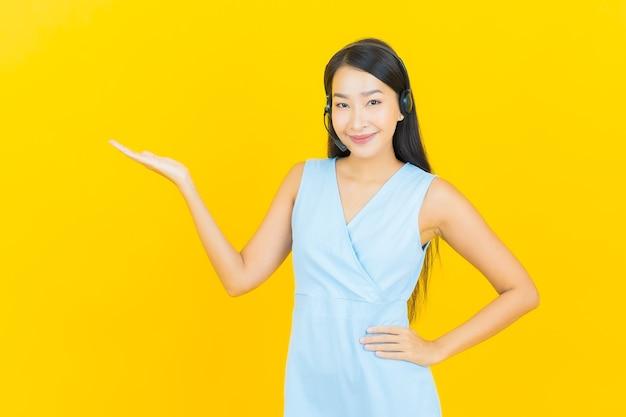 노란색 벽에 콜 센터 고객 관리 서비스 센터와 초상화 아름 다운 젊은 아시아 여자