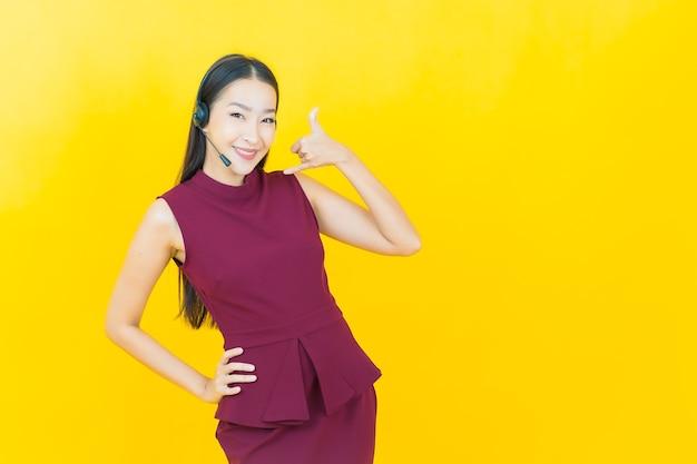 노란색 노란색 벽에 콜센터 고객 관리 서비스 센터가 있는 아름다운 젊은 아시아 여성 초상화