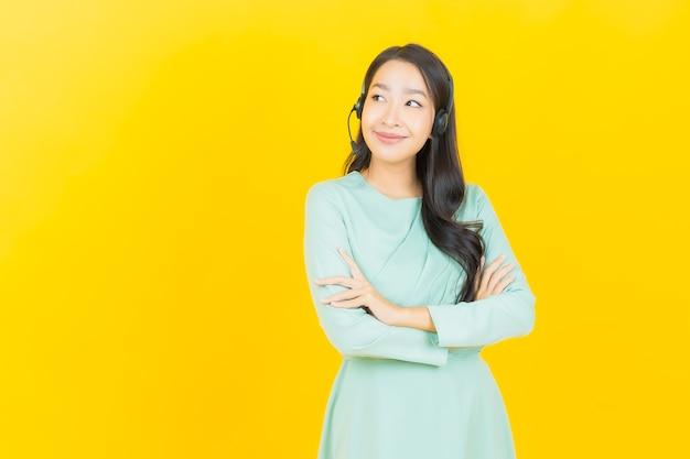 Женщина портрета красивая молодая азиатская с центром обслуживания клиентов центра телефонного обслуживания на желтом цвете