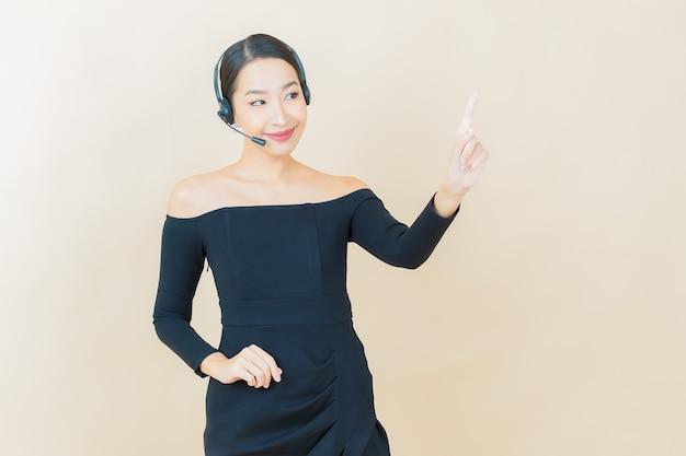 黄色のコールセンターカスタマーケアサービスセンターと肖像画の美しい若いアジアの女性