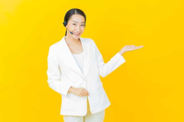 Portrait beautiful young asian woman with call center customer care service center on yellow color wall