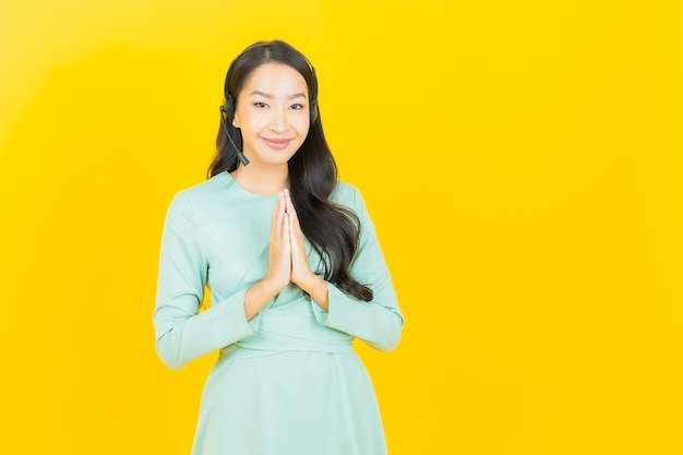 Portrait beautiful young asian woman with call center customer care service center on yellow