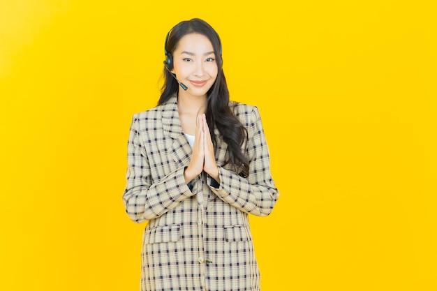 Женщина портрета красивая молодая азиатская с центром обслуживания клиентов центра телефонного обслуживания