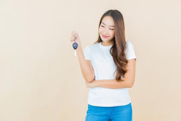 세로 베이지 색에 자동차 키와 아름 다운 젊은 아시아 여자