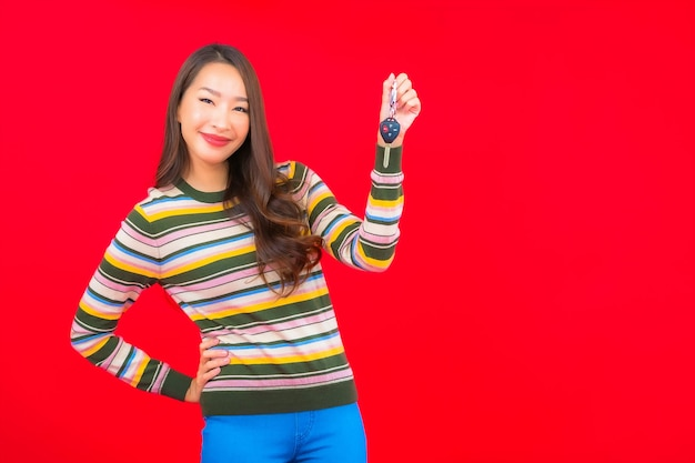 빨간색 격리 된 벽에 자동차 키 초상화 아름 다운 젊은 아시아 여자