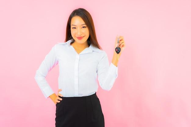 Bella giovane donna asiatica del ritratto con la chiave dell'automobile sulla parete isolata rosa
