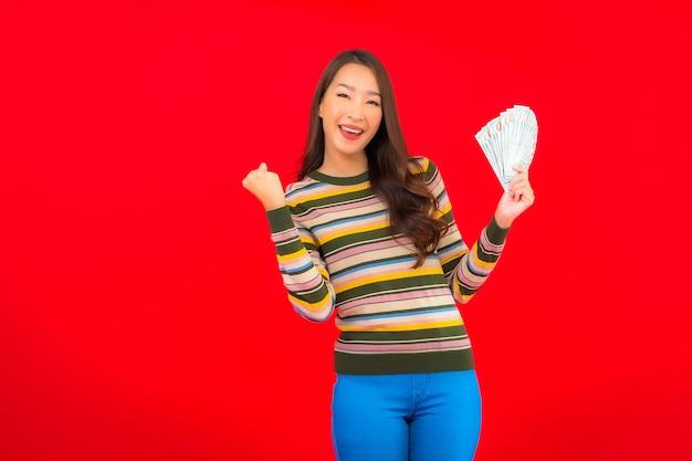 붉은 벽에 현금 돈과 휴대 전화 초상화 아름 다운 젊은 아시아 여자