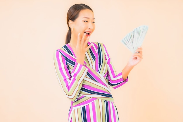 Portrait beautiful young asian woman with cash or money and mobile smart phone on color