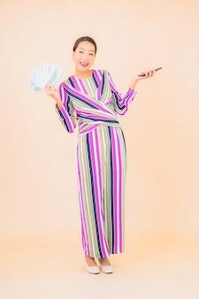 Bella giovane donna asiatica del ritratto con contanti o soldi e smart phone mobile sul colore