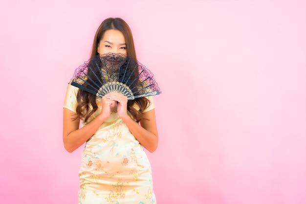 中国の旧正月のコンセプトと色の壁にファンを持つ美しい若いアジアの女性