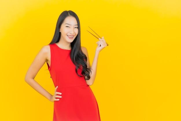 Bella giovane donna asiatica del ritratto con le bacchette pronte da mangiare sulla parete gialla