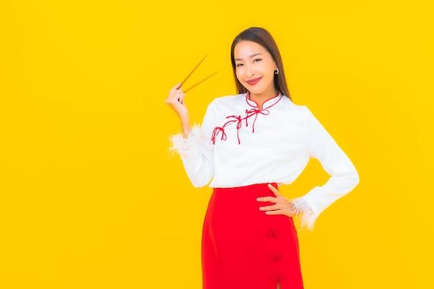 Ritratto bella giovane donna asiatica con bacchette pronto da mangiare su yellow