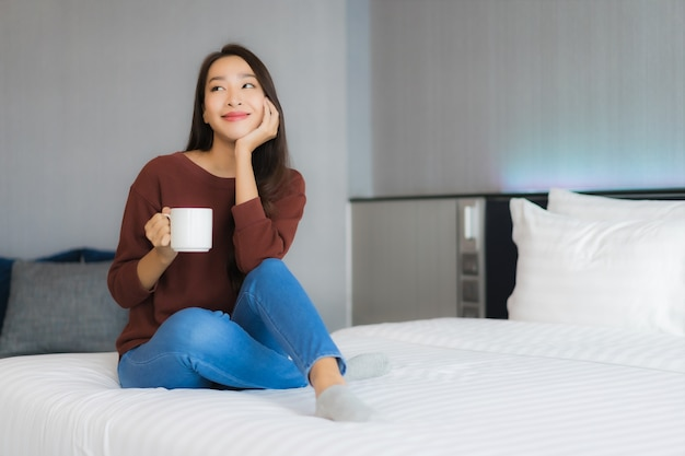 Portrait beautiful young asian woman with coffee cup on bed in bedroom interior
