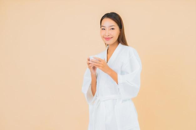 Bella giovane donna asiatica del ritratto con la tazza di caffè sul beige