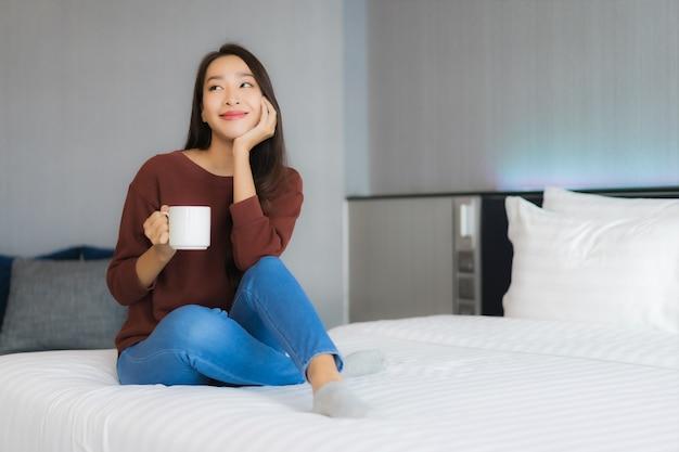 寝室のインテリアのベッドの上のコーヒーカップと美しい若いアジア女性の肖像画