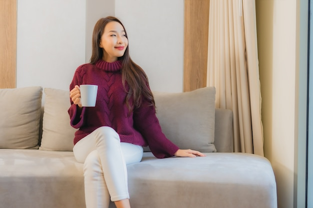 Женщина портрета красивая молодая азиатская с кофейной чашкой на интерьере украшения софы живущей комнаты