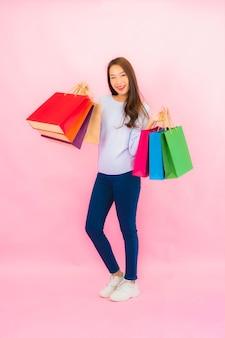 핑크 색상 고립 된 벽에 화려한 쇼핑 가방 초상화 아름 다운 젊은 아시아 여자
