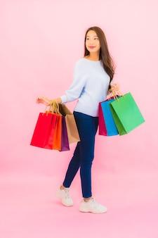 Bella giovane donna asiatica del ritratto con la borsa della spesa variopinta sulla parete isolata di colore rosa