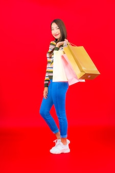 Portrait beautiful young asian woman with colorful shopping bag on red wall