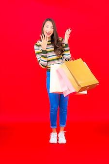 Bella giovane donna asiatica del ritratto con la borsa della spesa variopinta sulla parete rossa