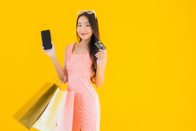스마트 폰 및 신용 카드와 화려한 쇼핑 가방 초상화 아름 다운 젊은 아시아 여자
