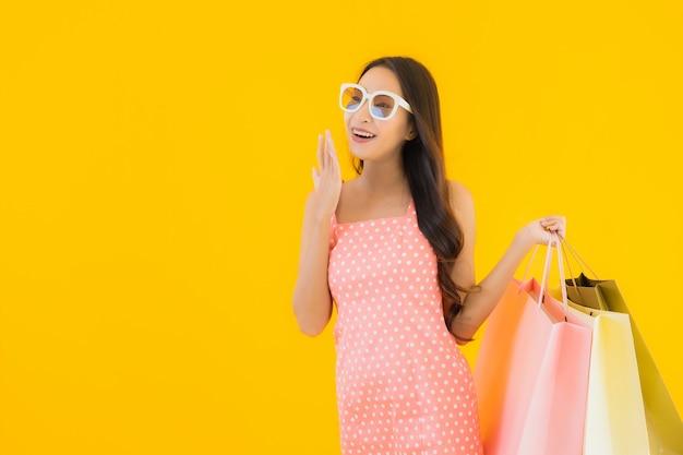 Bella giovane donna asiatica del ritratto con il sacchetto della spesa variopinto