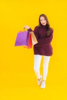 カラフルな買い物袋を持つ肖像画の美しい若いアジアの女性
