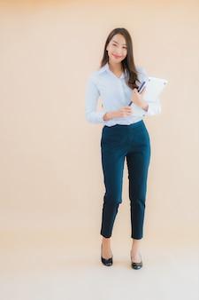 Женщина портрета красивая молодая азиатская с компьтер-книжкой компьютера для работы