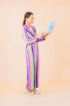 Женщина портрета красивая молодая азиатская с компьтер-книжкой компьютера на цвете