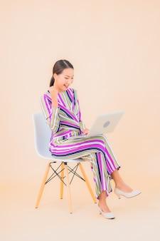色の上のコンピュータのラップトップを持つ肖像画美しい若いアジアの女性