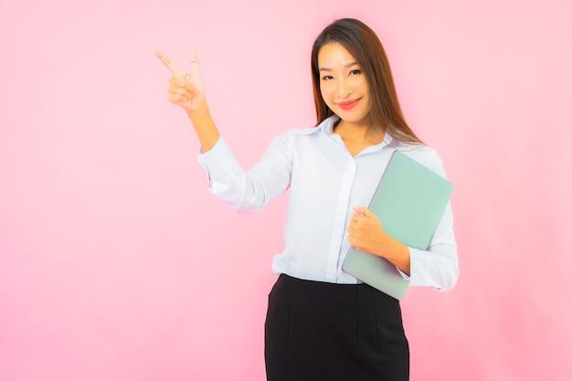 분홍색 벽에 컴퓨터 노트북을 들고 있는 아름다운 젊은 아시아 여성 초상화