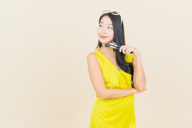 La bella giovane donna asiatica del ritratto con cosmeti compone la spazzola sulla parete di colore