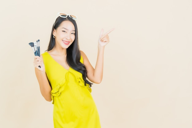 Portrait beautiful young asian woman with cosmeti make up brush on color wall