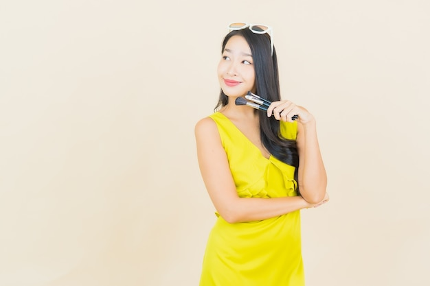 コスメティと肖像画の美しい若いアジアの女性は、色の壁にブラシを構成します