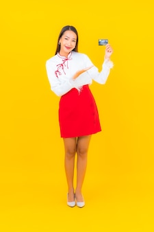 Портрет красивой молодой азиатской женщины с кредитной картой для онлайн-покупок на желтом